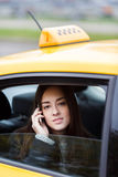 Young business woman talking on smartphone sitting in taxi Royalty Free Stock Photos