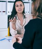 Smiling businesswoman talking to her colleague in office. royalty free stock photography