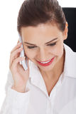 Young business woman with telephone, sitting by desk. Stock Photo