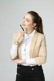 Young business woman thinking, holding pen in hand Royalty Free Stock Image