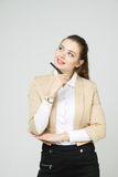 Young business woman thinking, holding pen in hand Stock Photos