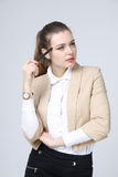 Young business woman thinking, holding pen in hand Royalty Free Stock Photos