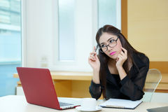 Young business woman thinking with a pen in hand at her workplac Royalty Free Stock Photo