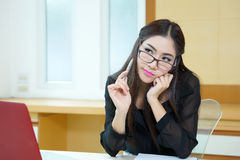 Young business woman thinking with a pen in hand at her workplac Royalty Free Stock Photos