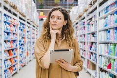 Young business woman is thinking about shopping with a tablet in hand in a supermarket.  Royalty Free Stock Photos