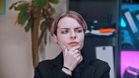 A young business woman thinking about something in the office