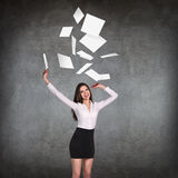 Young business woman throws up paper sheets. Stock Photo