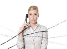Young business woman tied with phone cord. Young businesswoman sitting at a desk tied with phone cord, isolated stock photography