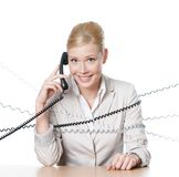 Young business woman tied with phone wire Royalty Free Stock Photography