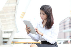 Young business woman touch on her tablet screen Stock Image