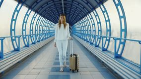 Young business woman with travel bag on wheels is on the transition from the terminal at the airport or train station.  stock footage
