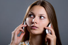 Young business woman with two mobile phones. In talks. Isolated over gray background Royalty Free Stock Photos