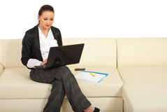 Young business woman typing on laptop. And sitting on sofa in office Royalty Free Stock Photos