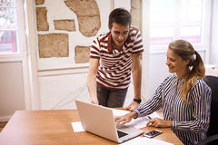 Young business woman typing on laptop. Young business women typing on laptop while young businessman, standing next to her is pointing to the screen Royalty Free Stock Photo