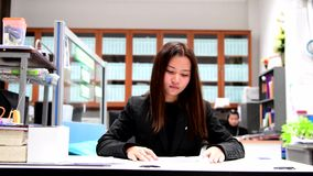 Young business woman unsatisfied report. Young business woman unsatisfied report at the desk on office background stock footage
