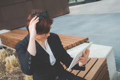 Young business woman use the tablet as a mirror in the financial district for business trip Royalty Free Stock Photo