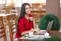 Young business woman uses laptop in cafe Stock Photos