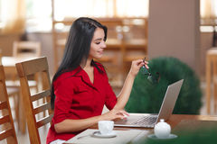 Young business woman uses laptop in cafe Royalty Free Stock Image
