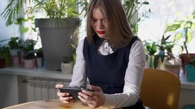 Young business woman using her smartphone in cafe with a lot of green plants. stock video footage