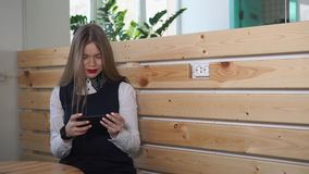 Young business woman using her smartphone. Young pretty business woman using her smartphone. She is browsing in the internet different information stock footage