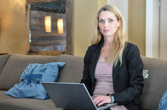A young business woman using a lap top. A beautiful young woman using a laptop in a public place Stock Images