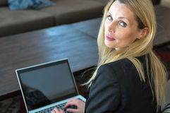 A young business woman using a lap top. A beautiful young woman using a laptop in a public place Royalty Free Stock Photos