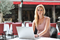 Young business woman using a lap top. A beautiful young woman using a laptop in a public place Royalty Free Stock Photos