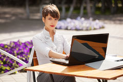 Young business woman using laptop at sidewalk cafe Royalty Free Stock Photography