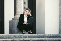 Young business woman using laptop on the steps Royalty Free Stock Photography