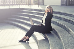Young business woman using laptop on the steps Royalty Free Stock Image