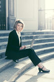 Young business woman using laptop on the steps Stock Image