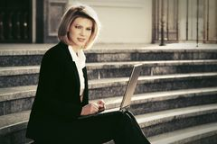 Young business woman using laptop on the steps Stock Photos