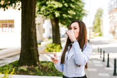 Young Business Woman Using Phone and Drinking Coffee While Walking. Alone Royalty Free Stock Images