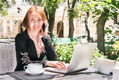 Young business woman is using smart phone and notebook in summer. Young business woman is using smart phone, notebook and drinking coffee in summer cafe of park Royalty Free Stock Photo