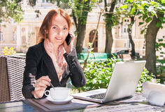 Young business woman is using smart phone and notebook in summer. Young business woman is using smart phone, notebook and drinking coffee in summer cafe of park Royalty Free Stock Image