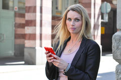 A young business woman using a smart phone outdoors. A beautiful young woman using a smart phone outside in a street Royalty Free Stock Image