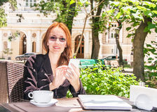 Young business woman is using smart phone in summer cafe. Young business woman is using smart phone and drinking coffee in summer cafe of park. Professional Stock Image