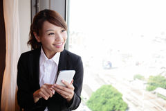 Young business woman using smart phone. Young business travle woman using digital tablet and smart phone in her hotel room, asian Royalty Free Stock Photos