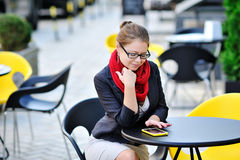 Young business woman is using smart phone for work in cafe Stock Images