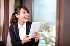 Young business woman using tablet pc. Young business travel woman using digital tablet and smart phone in her hotel room, asian Royalty Free Stock Photos