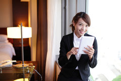 Young business woman using tablet pc. Young business travel woman using digital tablet and smart phone in her hotel room, asian Royalty Free Stock Photography