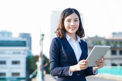 Young business woman using a tablet in the street with office bu Royalty Free Stock Images