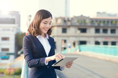 Young business woman using a tablet in the street. With office buildings in the background Stock Image