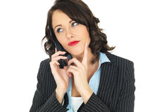 Young Business Woman Using a Telephone. A DSLR royalty free image, of an attractive young business woman, with brown curly hair, on a conference call talking Royalty Free Stock Photos