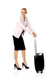 Young business woman waiting for travel with suitcase Stock Photo