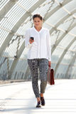 Young business woman walking with bag and mobile phone Stock Images