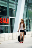 Young business woman walking outside of shopping plaza with her Royalty Free Stock Photos
