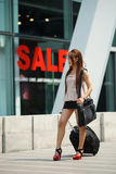 Young business woman walking outside of shopping plaza with her Stock Image