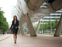 Young business woman walking on sidewalk Royalty Free Stock Image