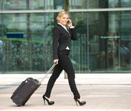 Young business woman walking and talking on phone in the city Royalty Free Stock Photos